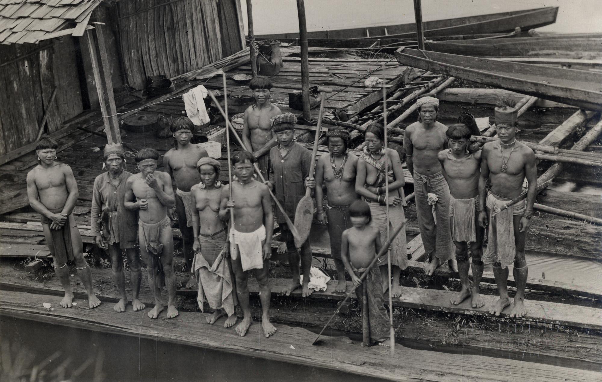 Vermoedelijk Poenan mannen en vrouwen op een steiger in een rivier op Oost-Borneo.  Presumably Poenan men and women on a jetty in a river in East Borneo.  Honda, M. Circa 1935.  Collection of Leiden University Libraries.